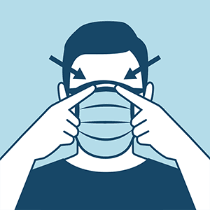 Frontal view of an individual wearing a cloth face covering. Individual is using two fingers to point to either side of the top of the nose, indicating that the covering fits well in this area.