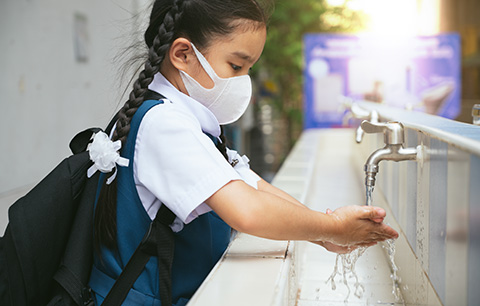 Student washing her hands at an outdoor wash basin.