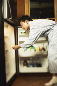 photo of man in front of open refrigerator