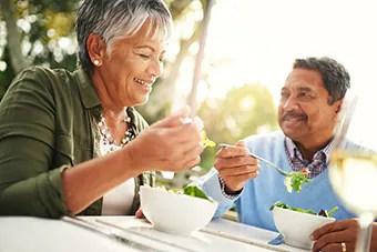 Couple eating salad outside