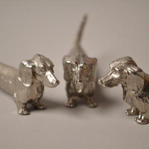 15 porte-couteaux en métal argenté en forme de chiens (teckels)