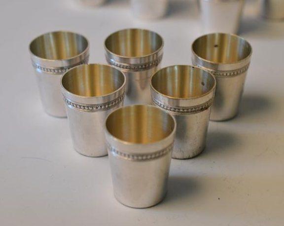 Douze verres à liqueurs en argent sur un plateau argenté