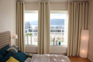Homestyling efterbild. Gardiner i fönster, gröna växter, en fin bäddad säng i naturfärger