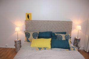 Homestyling efter bild. Sänglinne i linne och en beige pläd som sänggavel