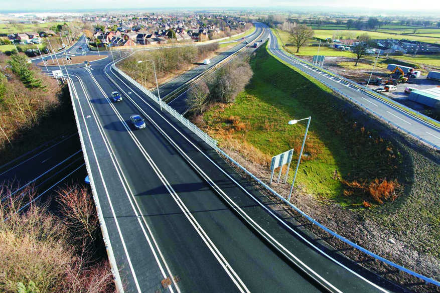 Figure 1 – Completed project looking east showing the new slip roads and eastern roundabout on the A5104, the retained vegetation and revised roadway on the bridge with new cycleway and footpath