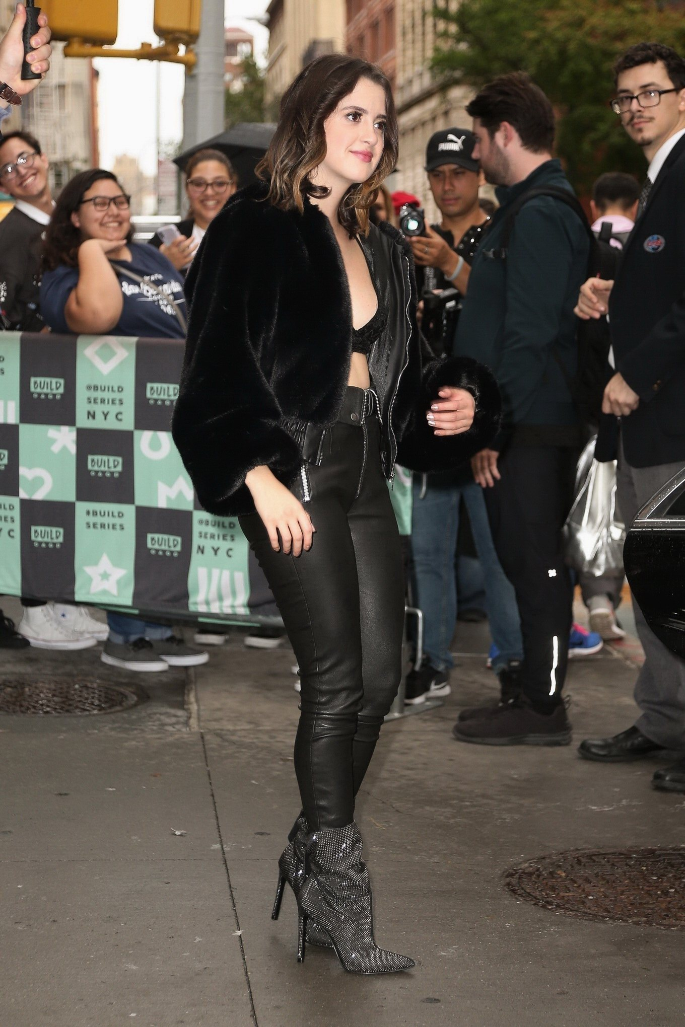 Laura Marano in a tiny black lace brawide open fur jacket