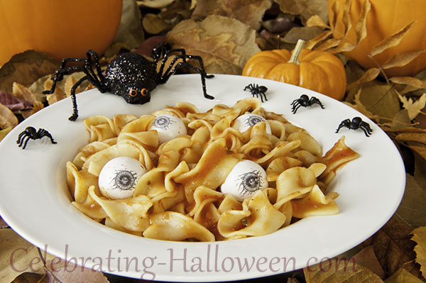 Zombie lunch of noodle brains and edible eyeballs with Halloween spiders