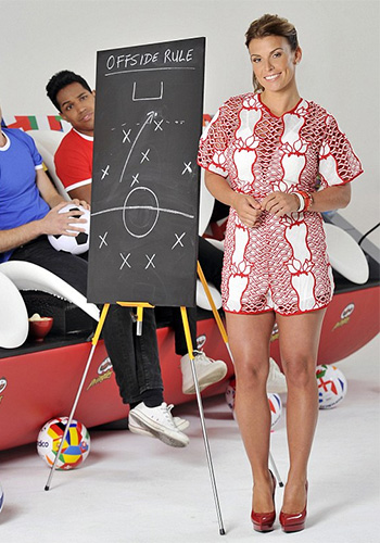 Coleen Rooney wears a Alice McCall Red Only This Moment Playsuit as she explains the offside rule in Football (Soccer) for Pringles UK.