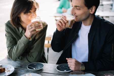 man and woman drinking coffee and negotiating relationship contract