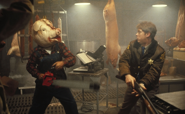 Photo of a scene from the movie Motel Hell, depicting a man wearing a pig head using a chain saw to menace a police officer