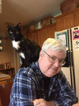 Photo of Mark Sieber with a cat on his shoulder