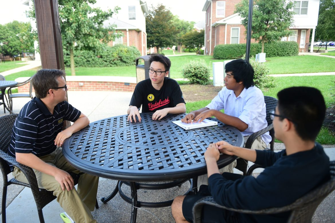 International students Duc Nguyen '18, Haoyi Guo '16 and Joy Joy (Khun Nyan Min Htet) '17 meet with student advisor Stephen Swan.
