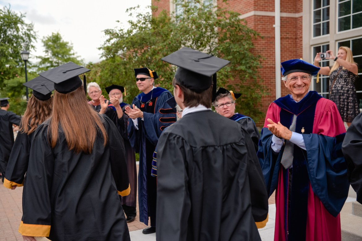 faculty applauding graduates as they process across campus