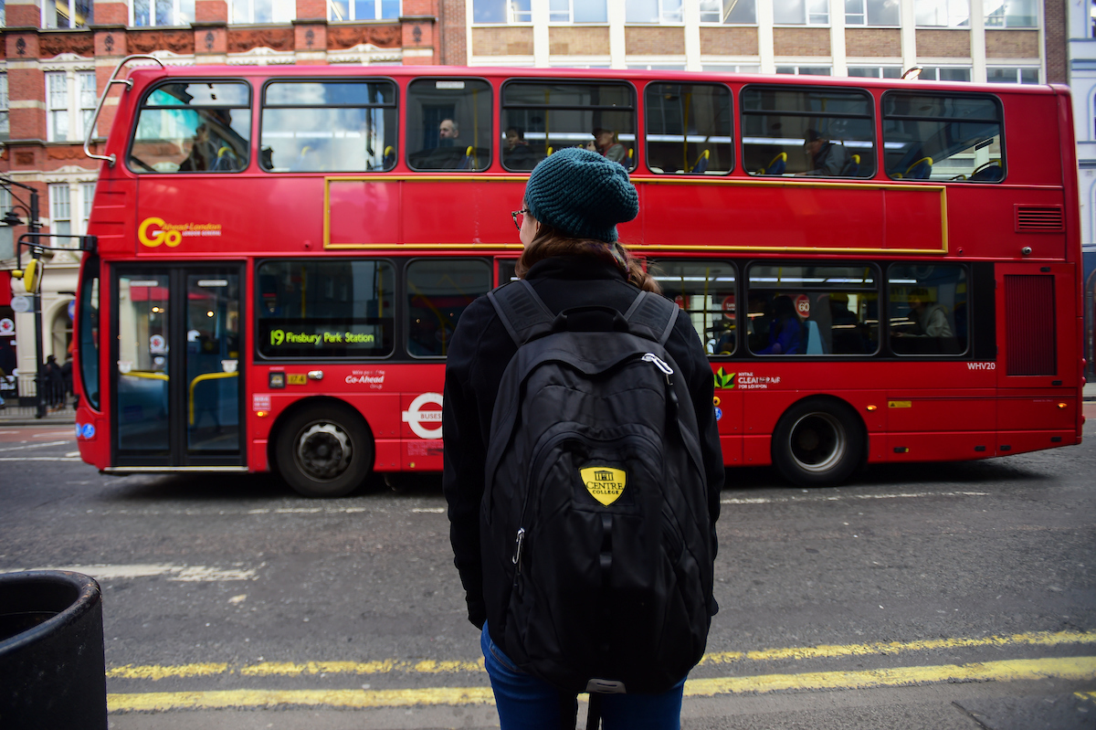 female student watching a double decker bus in London, England
