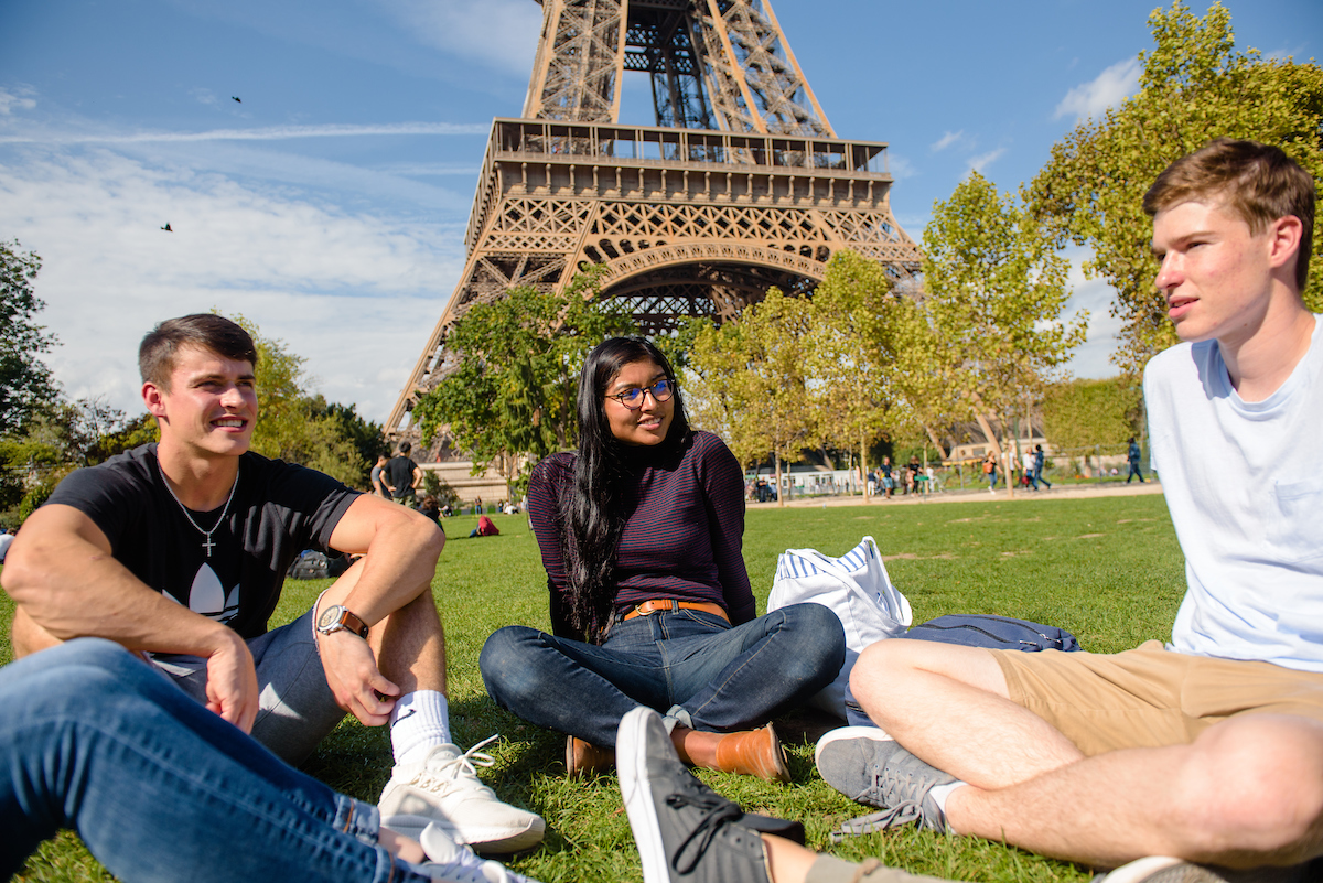 students sitting on the lawn in front of the Eiffel Tower in Paris