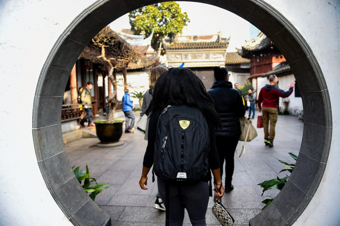 female student walks through a circular doorway in Shanghai, China