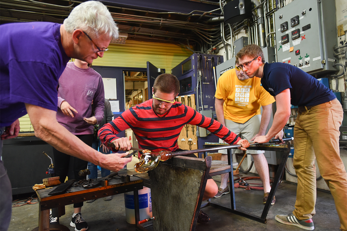 students creating a hot glass sculpture