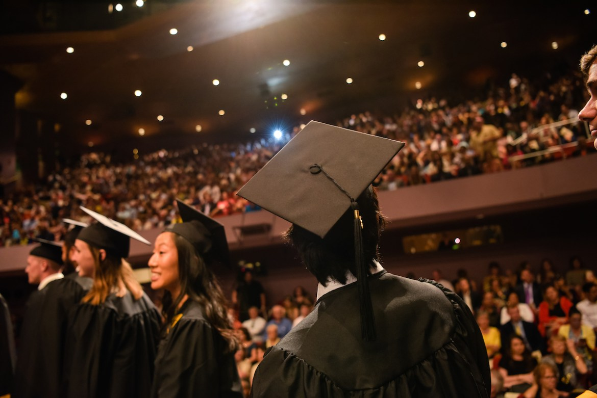 graduates look up at the audience at commencement