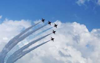 jet planes fly across the sky with smoke trails