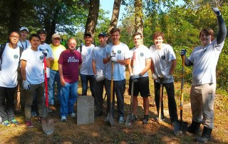 Student volunteer with garden tools at Shelby City African-American Cemetery