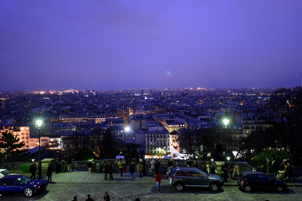 Students take in the view of Paris from Sacré-Cœur as the sun sets over the city.
