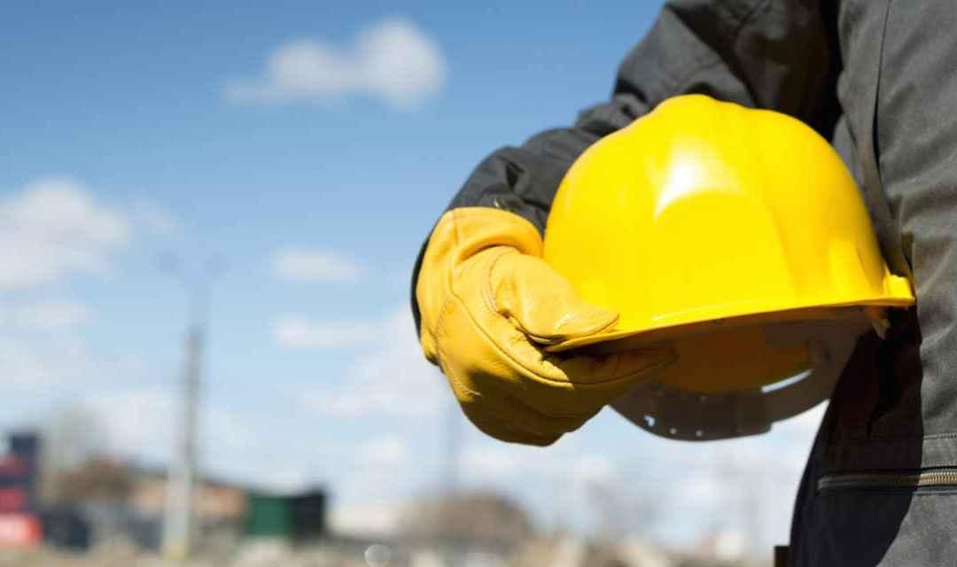 Uomo con casco antinfortunistica in mano