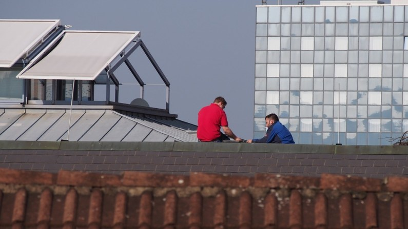two men on top of the roof