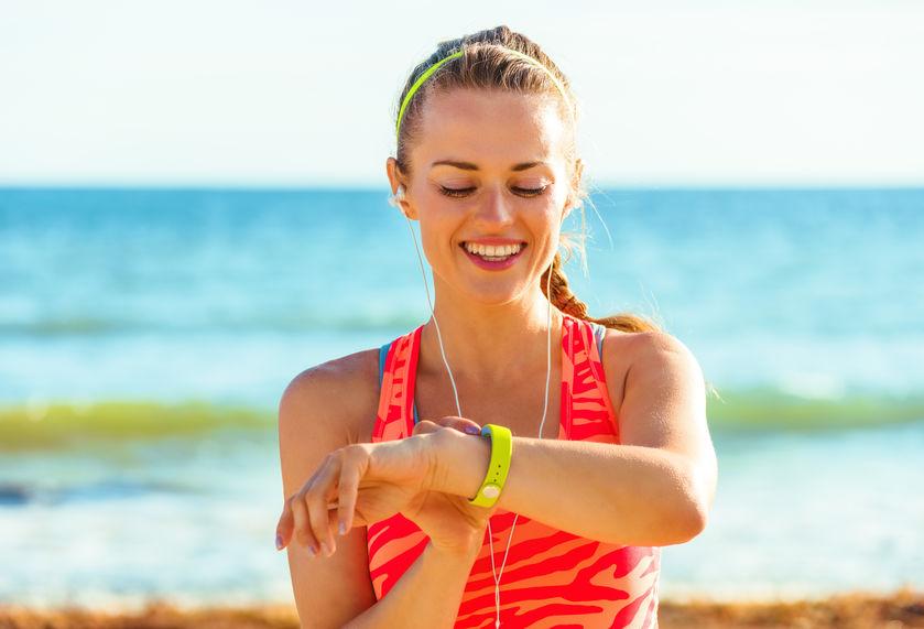 Donna con smartband sulla spiaggia