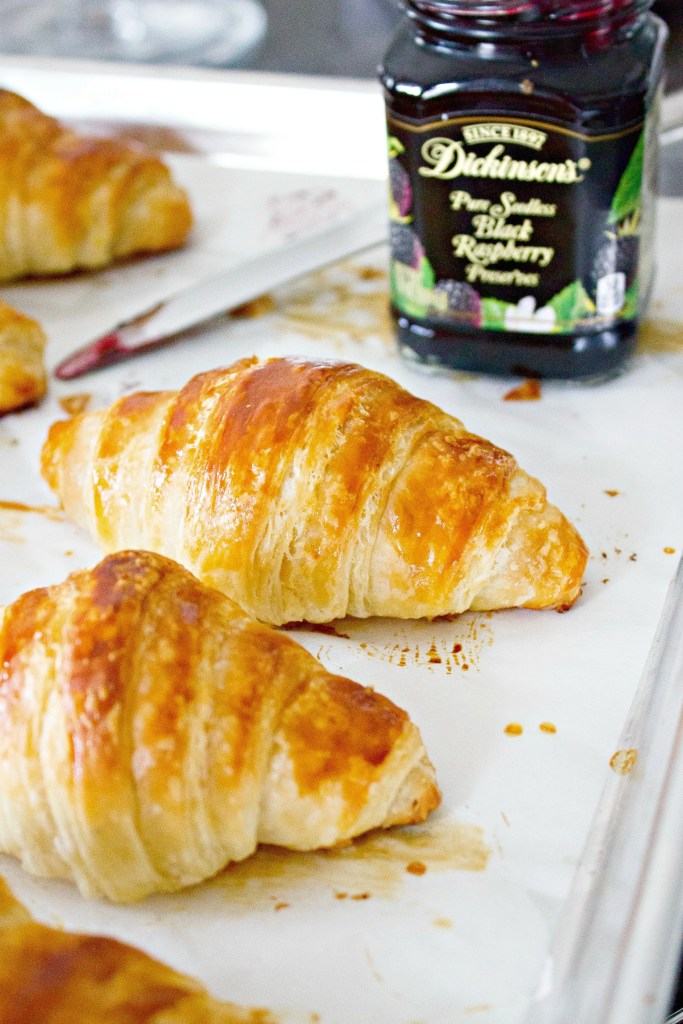 Classic Butter Croissants and a jar of black raspberry preserves on a baking sheet with parchment paper