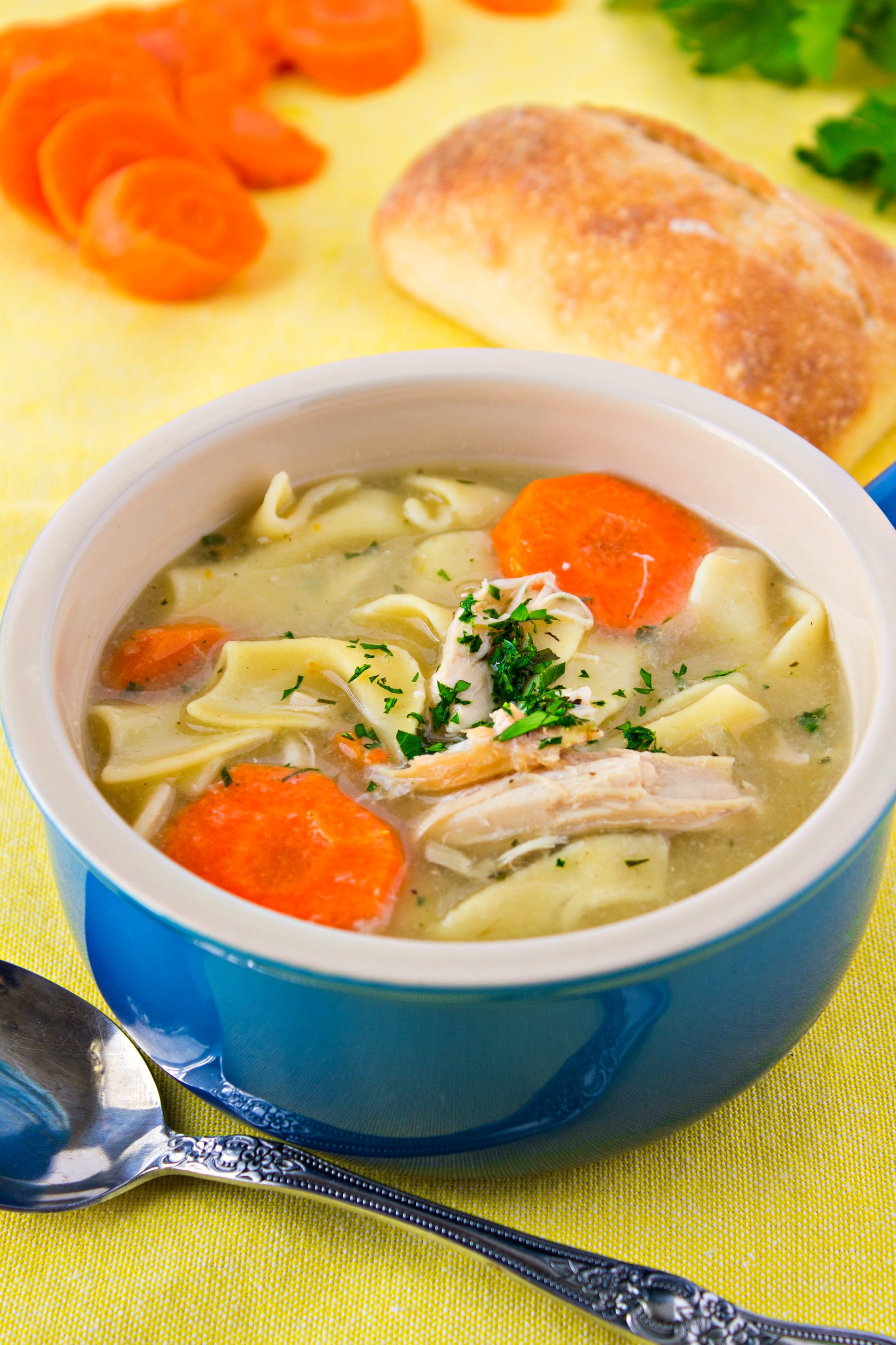 Bowl of Turkey Noodle Soup with bread and carrots in the background