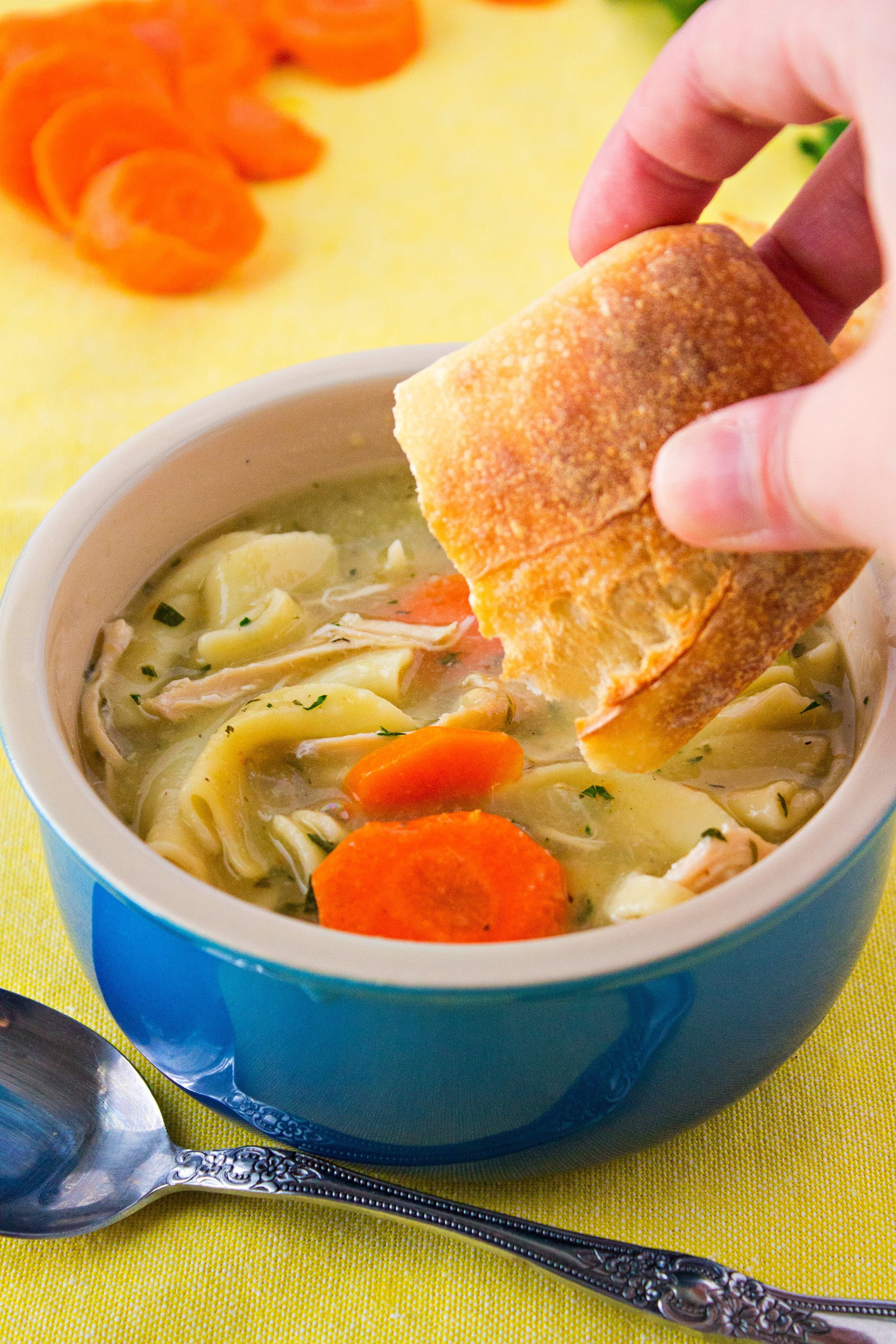 Dipping bread into Turkey Noodle Soup