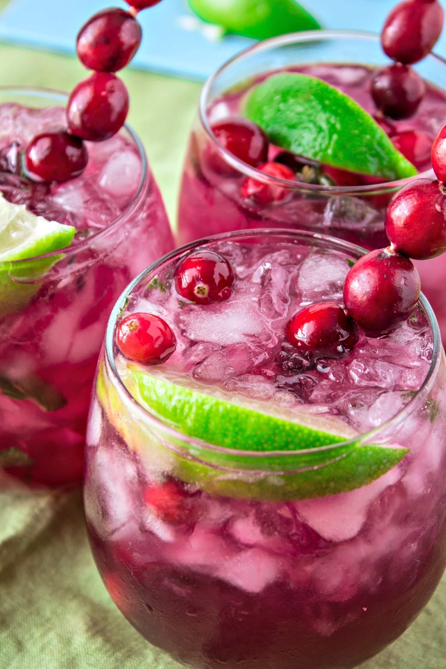 Three glasses of Cranberry Lime Mojitos with cranberry spears