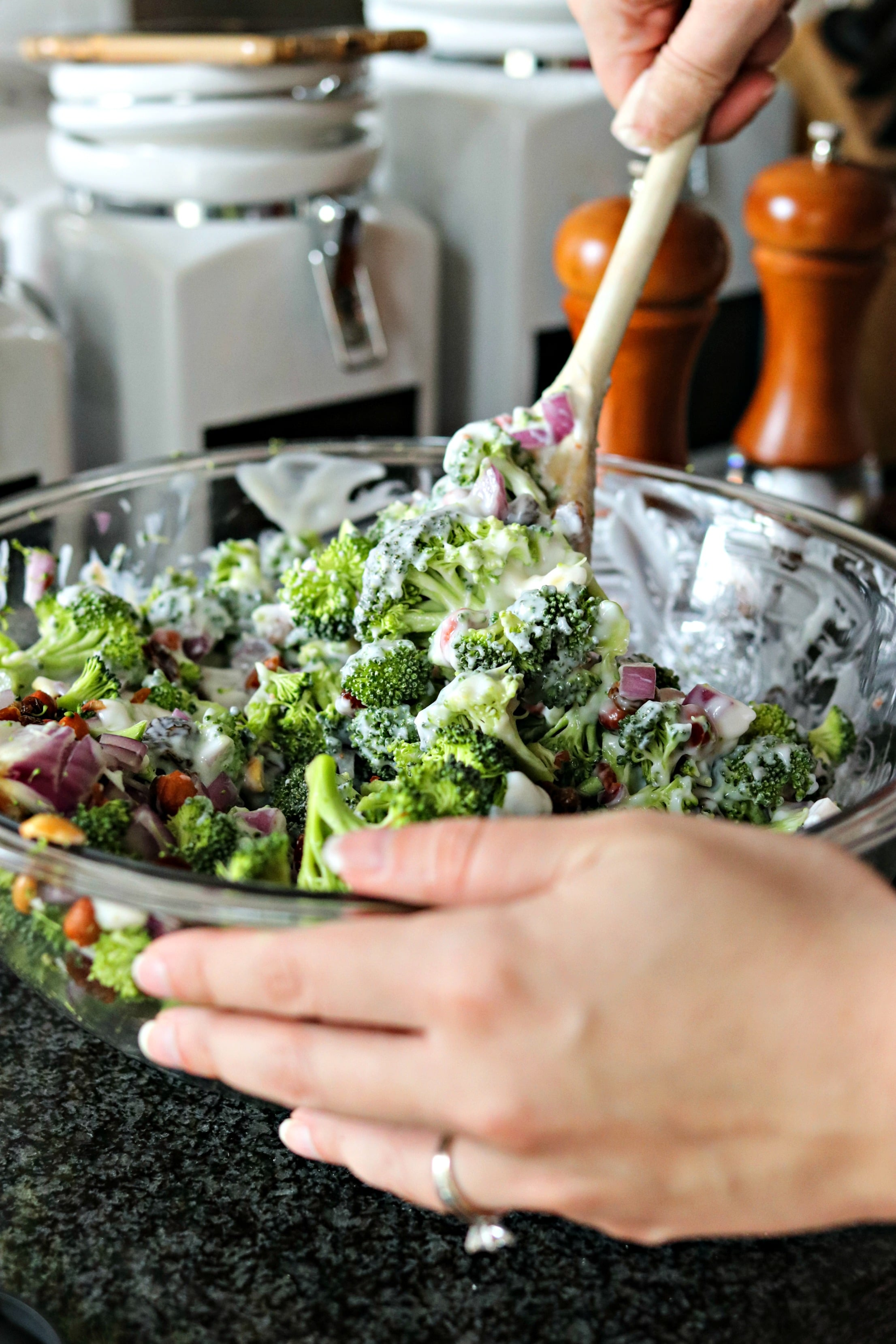 Mixing the dressing into the Fresh Broccoli Salad with Crispy Bacon