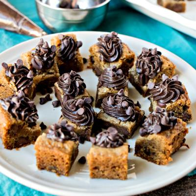 Chocolate Chip Cookies Bites with Fudge Frosting- Bite-sized pieces of chocolate chip cookies topped with fudge icing. It's fun, new way to serve cookies for your parties! And it's a great alternative to cookie cake.