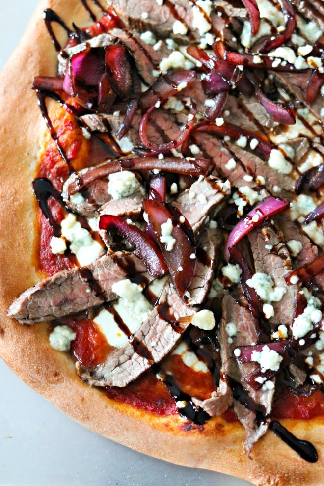 Steak & Blue Cheese Pizza - Spice up your pizza game with this steak and blue cheese pizza! Fresh pizza dough is topped with marinara, fresh mozzarella, caramelized red onions, grilled steak and blue cheese to make a dinner that is unforgettable!