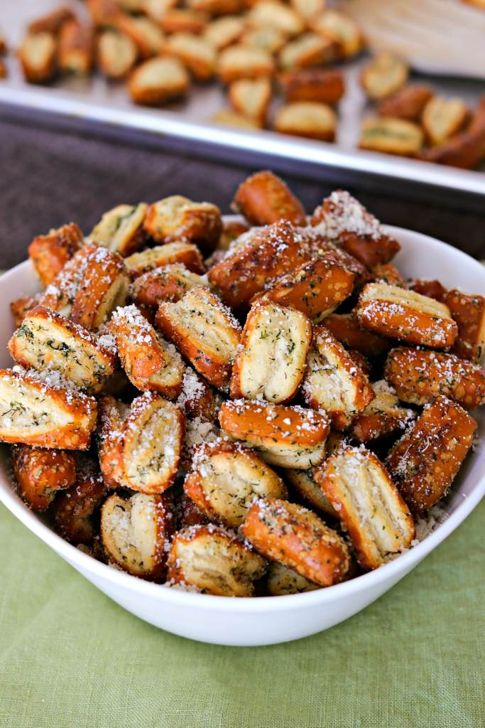 Easy Parmesan Garlic Pretzels in a bowl with a pan of pretzels behind it