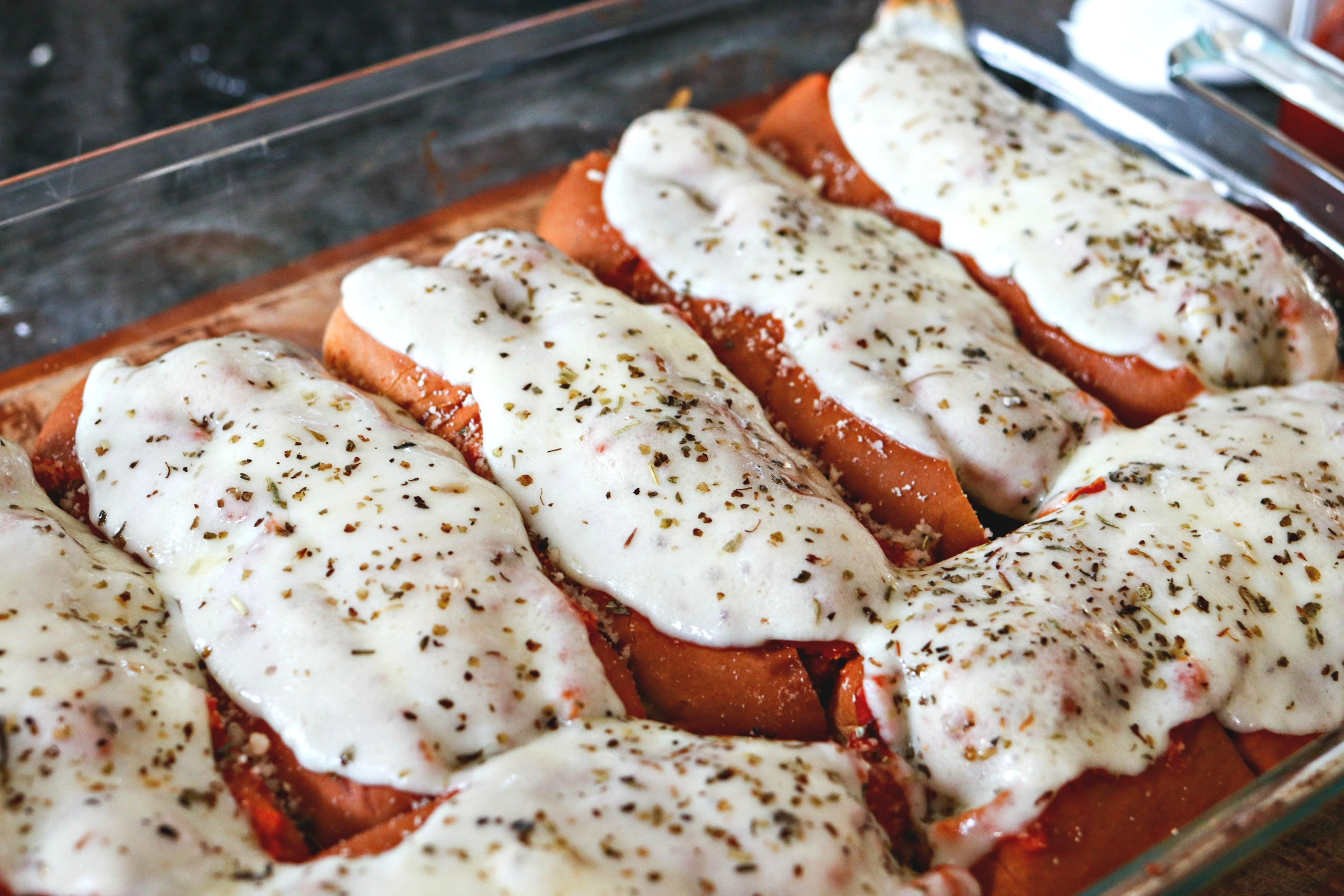 Easy Meatball Subs with melted cheese and herbs on top