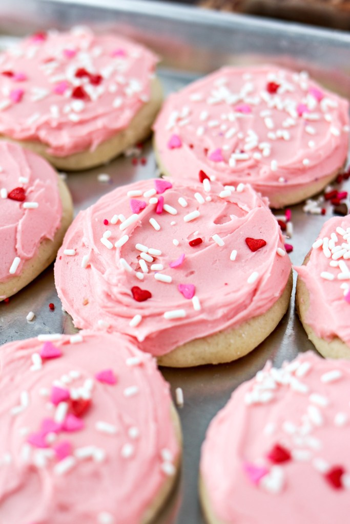 Soft Frosted Sugar Cookies on a baking sheet with sprinkles on top