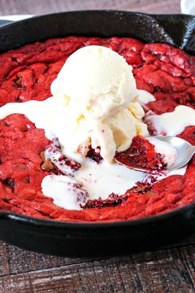 Red Velvet Skillet Cookie in a cast iron pan with vanilla ice cream on top