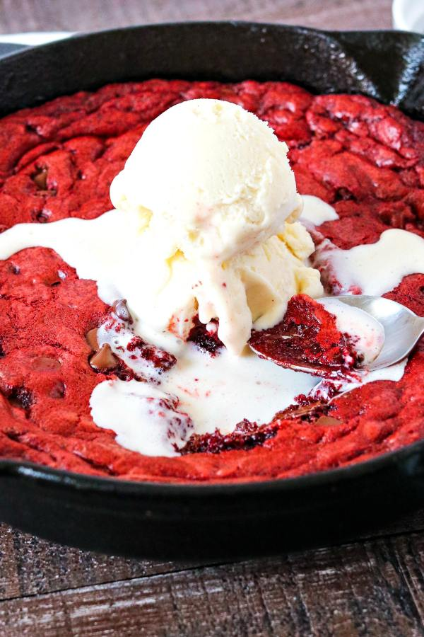Red Velvet Skillet Cookie - A warm red velvet cookie with an ooey gooey center and chocolate chips mixed throughout. Once you try a bite of this dessert, you won't want to share!