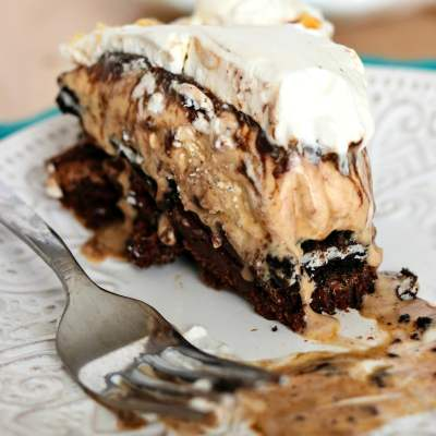 a slice of The Ultimate Brownie Sundae pie on a plate with a bite taken out of it