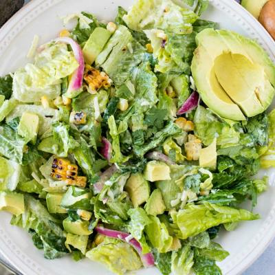 Avocado and Charred Corn Salad with Cilantro Ranch Dressing - A refreshing and filling salad, made with leafy greens, diced avocado, charred corn, pickled red onions, diced cucumbers, shredded Monterrey Jack cheese, and chopped cilantro, tossed with a homemade cilantro ranch dressing.