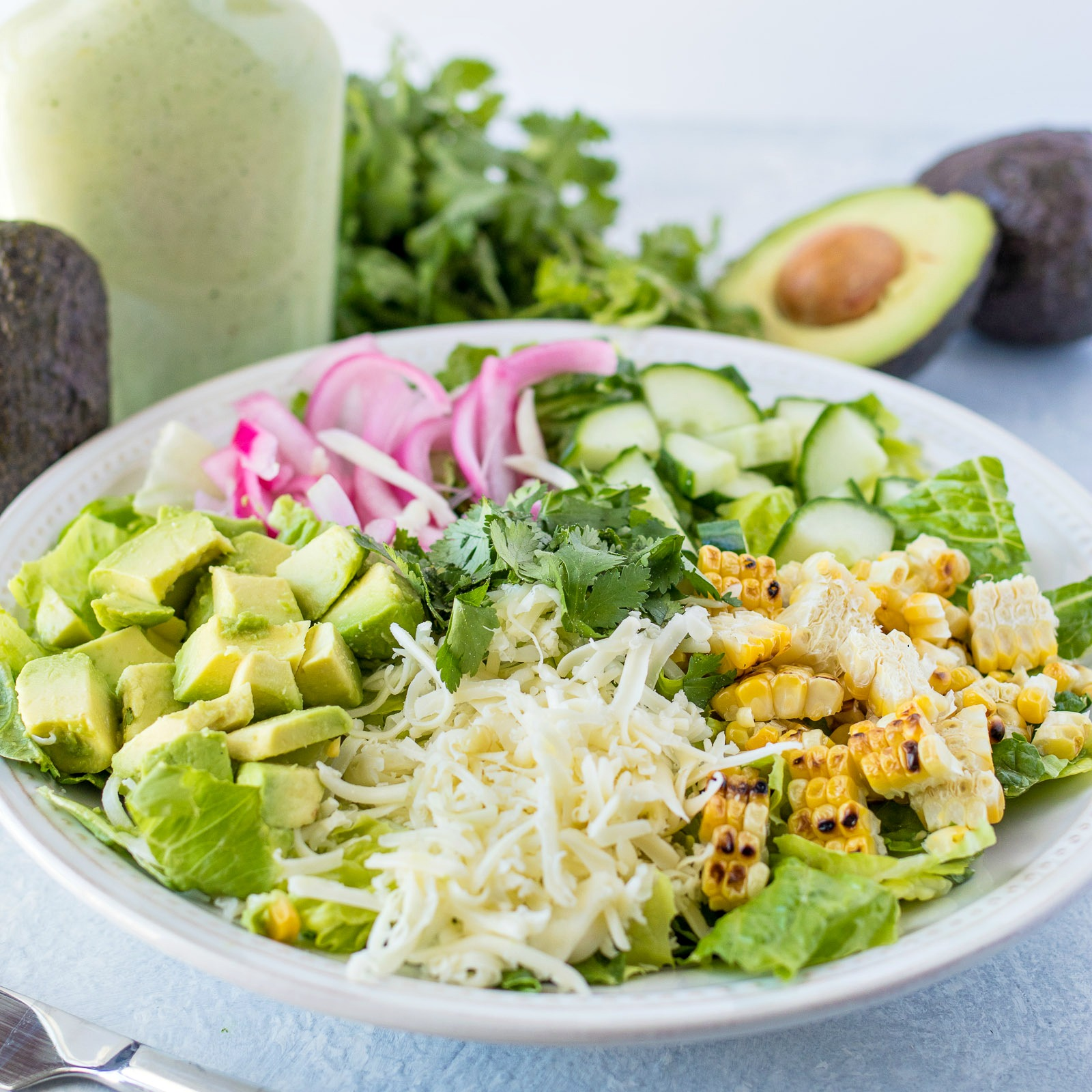 Avocado and Charred Corn Salad with Cilantro Ranch Dressing -A refreshing and filling salad, made with leafy greens, diced avocado, charred corn, picked red onions, diced cucumbers, shredded Monterrey Jack cheese, and chopped cilantro, tossed with a homemade cilantro ranch dressing.
