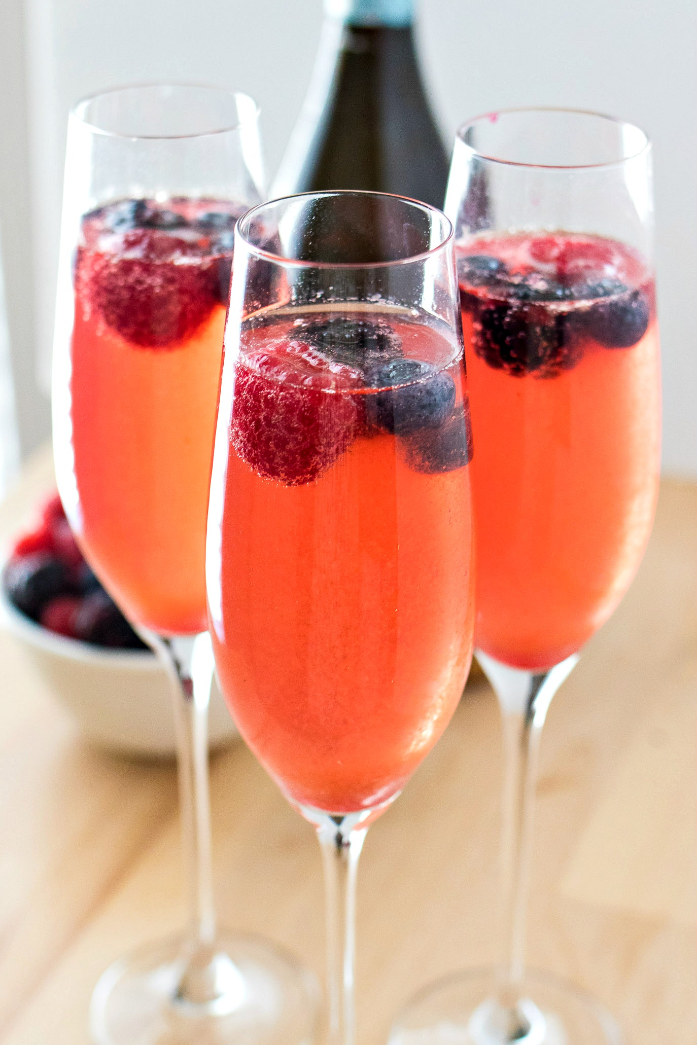 Three champagne flutes of Berry Mimosas