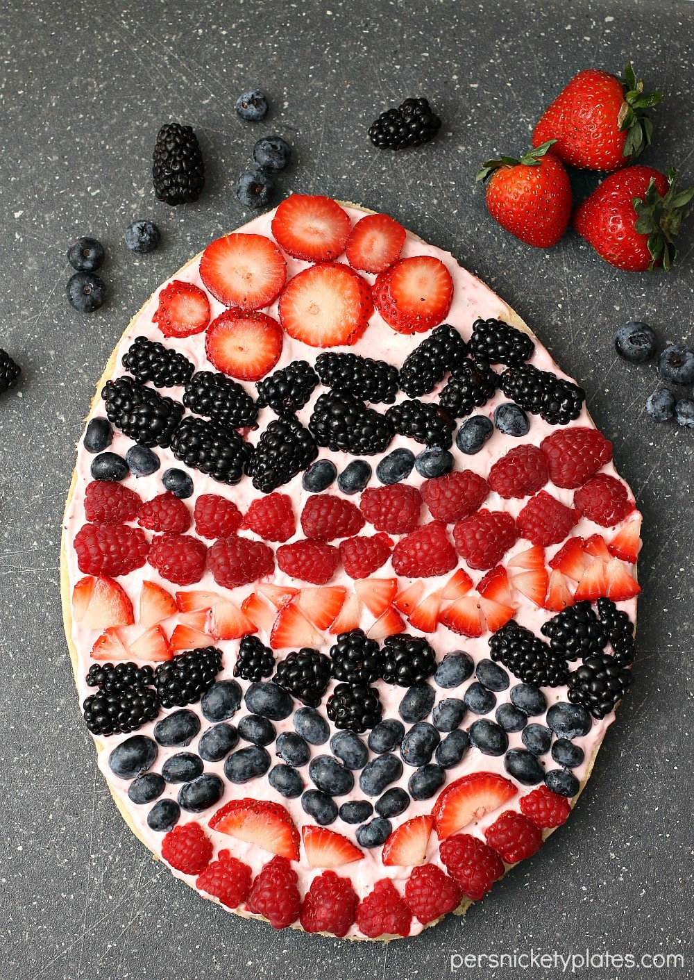 Fruit Pizza in the shape of an easter egg, with fruit forming stripes