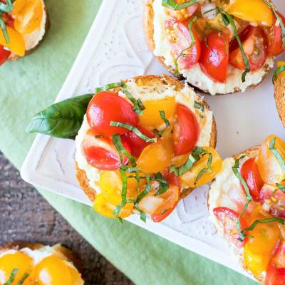 Tomato & Whipped Feta Crostini - Crispy baguette rounds spread with a creamy layer of lemony whipped feta cheese and topped with juicy cherry tomatoes soaked in a tangy vinaigrette. This is the best appetizer you will ever make - you won't be able to stop eating it!