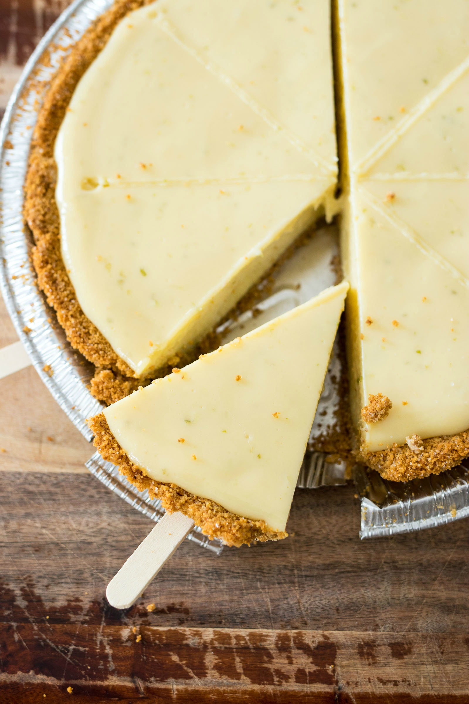 Slice of key lime pie with a popsicle stick stuck in the crust side