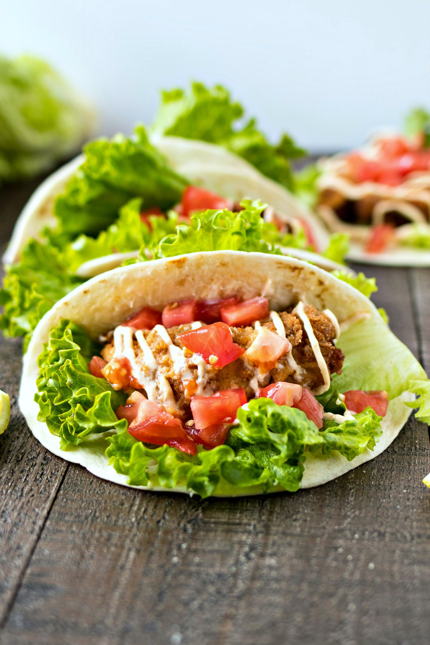 Fried Chicken Tacos - A crispy buttermilk fried chicken tender wrapped in leafy lettuce and a flour tortilla and finished with juicy diced tomatoes and a lemon garlic mayo. A simple, yet delicious new way to get your taco fix on Taco Tuesday!
