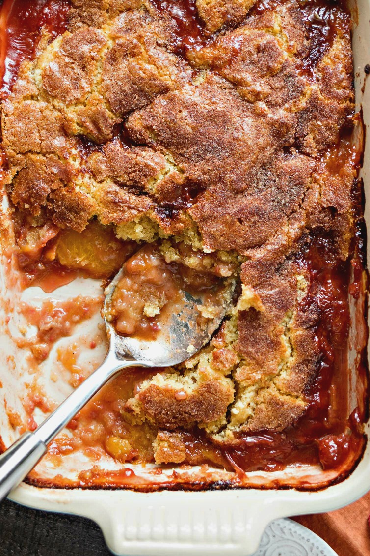 Peach Raspberry Cobbler - A Southern peach cobbler given a little twist with the addition of fresh raspberries and a cinnamon sugar crust. The cakey, yet crispy crust is so spectacular that you won't even need ice cream for this incredibly comforting dessert!