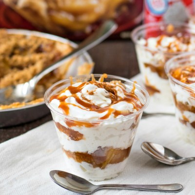 styled shot of Salted Caramel Apple Pie Parfaits with a pan of pie and a can of whipped cream behind it